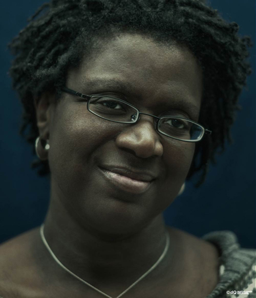 Portrait of a black smiling woman wearing reading glasses SKU: po-0005